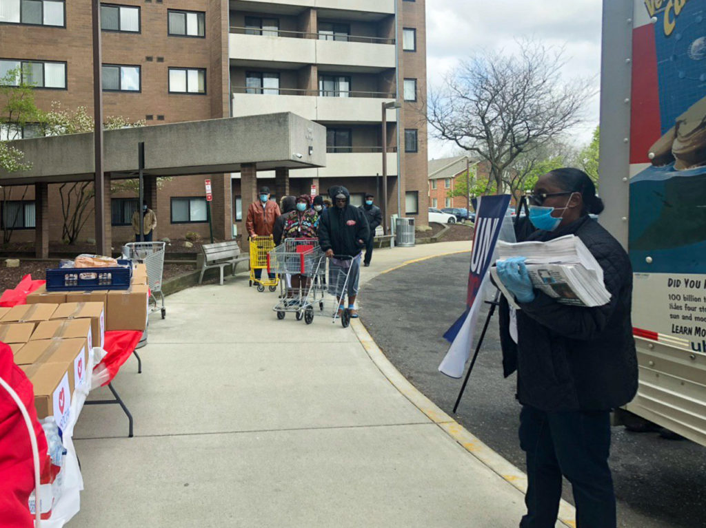 With gloves and masks, volunteers prepare to receive the residents of this Detroit community